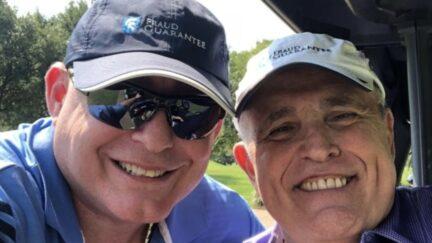 Lev Parnas and Rudy Giuliani wearing Fraud Guarantee hats